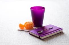 Taccuino, tazza, mandarino e cucchiaino da tè Fotografie Stock Libere da Diritti