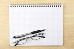 Taccuino, vetri e penna immagine stock