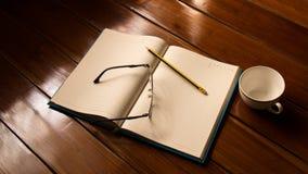 Taccuino, vetri, matita e tazza Fotografia Stock Libera da Diritti
