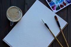 Taccuino vuoto bianco con le spazzole e un insieme dei colori e una tazza di caffè su una tavola nera Immagini Stock