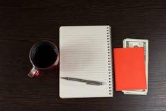 Taccuino vuoto con le banconote del dollaro e della penna sullo scrittorio di legno Con lo spazio della copia Fotografia Stock