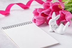 Taccuino vuoto, coniglietto di pasqua sveglio e tulipani rosa immagine stock libera da diritti