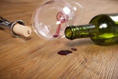 Tache de vin rouge sur le plancher en bois, verre de vin sale, tire-bouchon, bouteille de vin vide Photos stock