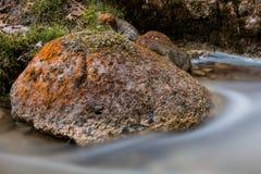 Tache floue de l'eau autour de roche colorée dans The Creek Images libres de droits
