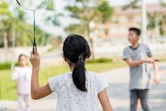 Tache floue de mouvement de retour de la fille jouant le badminton images stock