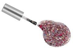 Tache transparente de vernis à ongles avec les particules rouges et diverses de scintillement et la brosse colorées d'application photographie stock libre de droits