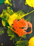 Taches de peinture sur le fond noir avec la peinture jaune, orange et verte Photos stock