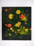 Taches de peinture sur le fond noir avec la peinture jaune, orange et verte Photos libres de droits