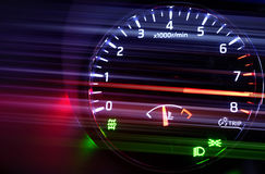 Tachometer with hi speed in dark. Closeup photo of modern automotive tachometer with hi speed on black background, motion blur filter effect Royalty Free Stock Image