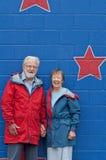 Tachtig éénjarigenpaar in regenjassen dichtbij blauwe muur Stock Foto's