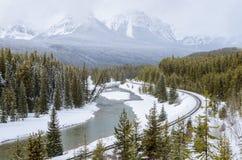 Tachuela ferroviaria a lo largo del lado un río en un paisaje de la montaña en invierno foto de archivo