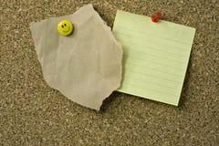 Tachuelas y notas de pulgar sobre corkboard Fotos de archivo libres de regalías