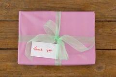 Tacka dig att card med gåvaasken på tabellen royaltyfri foto