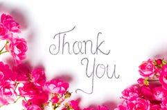 Tacka dig att notera med rosa rosor på vit arkivfoton