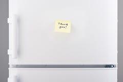 Tacka dig att notera på gult klibbigt papper på det vita kylskåpet arkivfoton