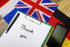 Tacka dig att smsa skriftligt på papper på det trätextural skrivbordet med folkhop arkivbild