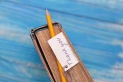 Tacka dig att underteckna på pancil och den gamla boken - tappningstil royaltyfri foto