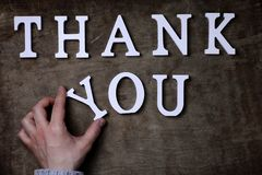 Tacka dig att uttrycka från vita träbokstäver på tabellen och händer arkivbild