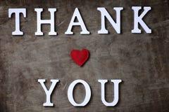 Tacka dig att uttrycka från vita träbokstäver på tabellen och händer arkivfoton