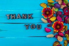 Tacka dig att uttrycka på blått trä med blomman arkivfoton
