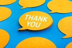 Tacka dig begrepp med pratstund, anförandebubblasymboler på blå färgbakgrund royaltyfri foto