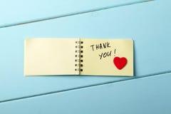 Tacka dig, den spiral notepaden för A som har ordden träröda hjärtan royaltyfri bild