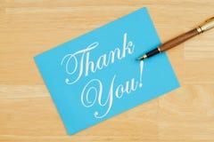 Tacka dig det blåa hälsa kortet med en penna på texturerat trä arkivfoton