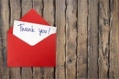 Tacka dig för att card och kuvertet på träbakgrund royaltyfri bild