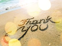Tacka dig inskriften på den sandiga havsstranden royaltyfria foton