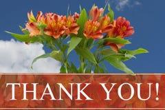 Tacka dig meddelandet med en apelsin och gulna liljabuketten royaltyfri fotografi