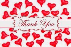 Tacka dig meddelandet med röda hjärtor på vitt tyg royaltyfri bild