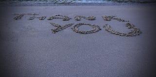 Tacka dig meddelandet som är skriftligt i sand Arkivbilder
