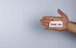 Tacka dig på litet vitt stycke av papper i hans handman arkivfoto