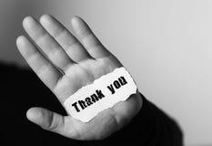 Tacka dig på litet vitt stycke av papper i hans handmanmonochro fotografering för bildbyråer