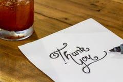 Tacka dig - räcka handstiltext på trä arkivfoto