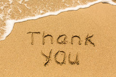 Tacka dig - som är skriftlig manuellt på texturen av havssand arkivfoton