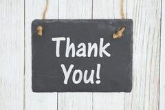 Tacka dig text på en hängande svart tavla på ridit ut bortförklaringen texturerat trä arkivfoton