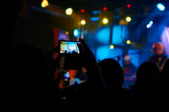 Tacke picture at the rock concert. Take photos with mobile phone during rock concert Stock Photo