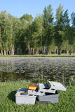 Tackle box by pond. Open tackle box on the bank of a pond stock image