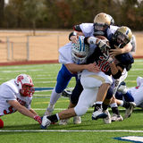 Tackle football. A ball carrier gets tackled by a swarm of defenders during the Texas Association of Parochial and Private Schools (TAPPS) Division 1 All-star Stock Photography