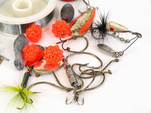 Tackle and Hooks. Various fishing lures, bait and a spool of line over a white background Stock Photography