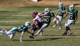 Tackled. American football players in a game on Saturday afternoon in Redding, California. Shasta College (green) vs. Gavilan College Stock Photography