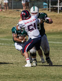 Tackled. American football players in a game on Saturday afternoon in Redding, California. Shasta College (green) vs. Gavilan College Stock Images
