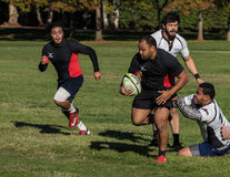 Almost Tackled. Redding, California- November 7, 2015:  A Blackhawk player (black jersey) runs past Shasta players in a match between Shasta HIghlanders and Royalty Free Stock Photo