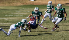 Tackled Roughly. American football players in a game on Saturday afternoon in Redding, California. Shasta College (green) vs. Gavilan College Royalty Free Stock Photos