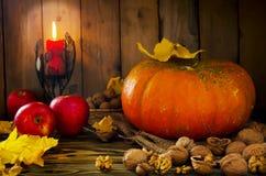 Tacksägelse - pumpa, muttrar, äpplen med levande ljus arkivbild