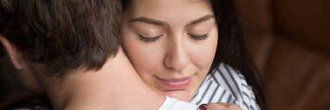 Tacksam fru för Closeupkvinnaframsida med stängda ögon som omfamnar maken arkivbild