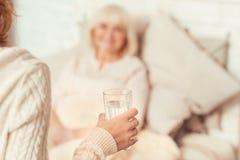 Tacksam kvinna som att bry sig exponeringsglas av vatten för avgådd dåligt farmor Royaltyfri Foto
