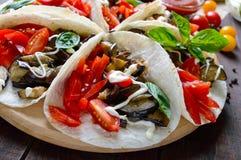 Taco är ett traditionellt mexicanskt mellanmål Aubergine söta peppar, tomater i pitabröd Royaltyfri Bild