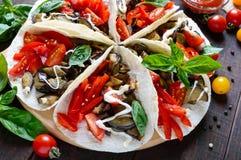 Taco är ett traditionellt mexicanskt mellanmål Aubergine söta peppar, tomater i pitabröd Arkivbild